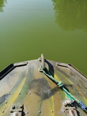 the bow of the metal boat fishing on the background of water