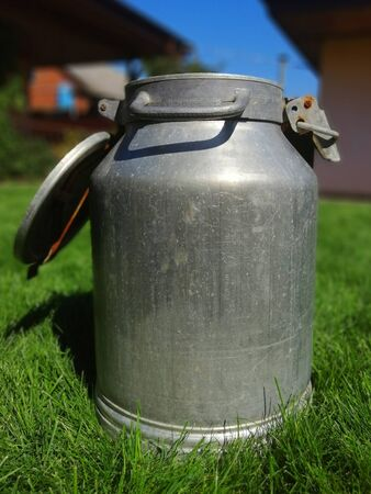 metal can for liquids with an open lid. in sunny weather on the grass. the idea of a healthy diet. close-up Banco de Imagens