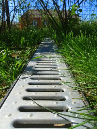 drainage systems. idea - building a house, storm taps. metal construction from the roof - sewer and grate on the ground for draining water closeup. sunny day, green grass