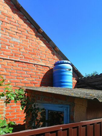 blue barrel. on the roof against the blue sky and red brick. sunny day. improvement of a private house. container made of plastic for heating water, outdoor shower Banco de Imagens