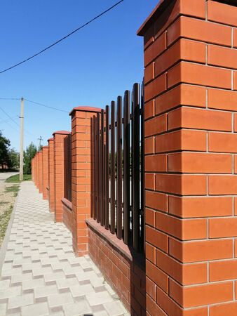 fence of red brick and metal vertical stripes - shtaketin. perspective view against the blue sky. idea - building a private house