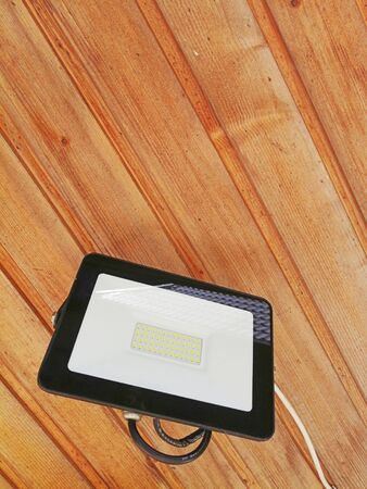 LED floodlight, rectangular, black. the idea is street lighting. bottom view, wooden background. place for text Banco de Imagens