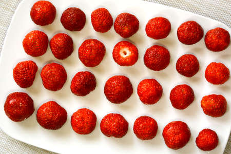 Strawberries lie in rows on a plate on a white background. The view from the top. One berry is upside down. 写真素材