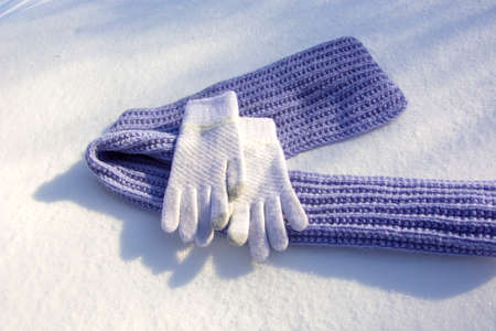 Winter sunny day. Knitted scarf and gloves lie in the snow. Clothing accessories for warmth in winter. Lilac pancake scarf along with white mittens top view. Winter background with knitted warm clothe