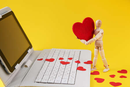 Dating Online. Wooden mannequin and hearts using laptop depicts communication internet. Supporting customers Concept.