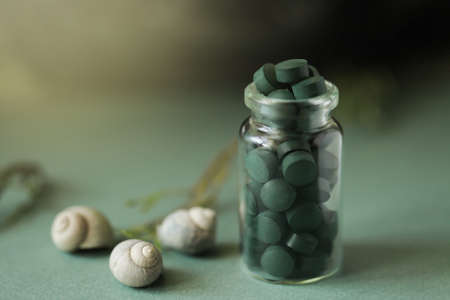 Spirulina pills in glass bottle, sea shells on green background. Antioxidant nutrition. Bio-energy, biofuel, energy research. Copy space