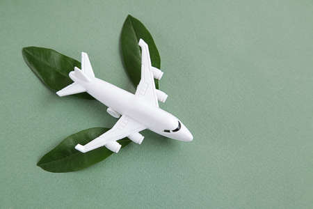 White airplane model emitting fresh green leaves on green background. Sustainable travel, clean and green energy, biofuel for aviation industry concept. Copy space