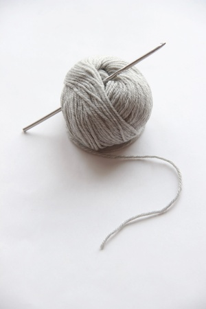 unravel: Gray ball of string on a white background with crochet