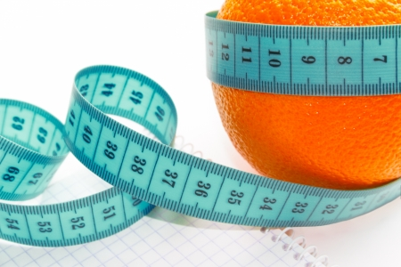 Fruit and measuring tape to the body on a white background photo