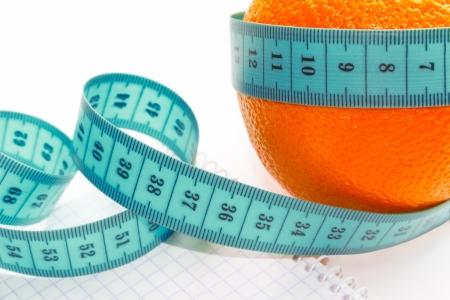 cinta metrica: Frutas y cinta m�trica para el cuerpo sobre un fondo blanco