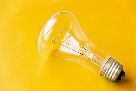 Close-up incandescent light bulb on yellow  photo