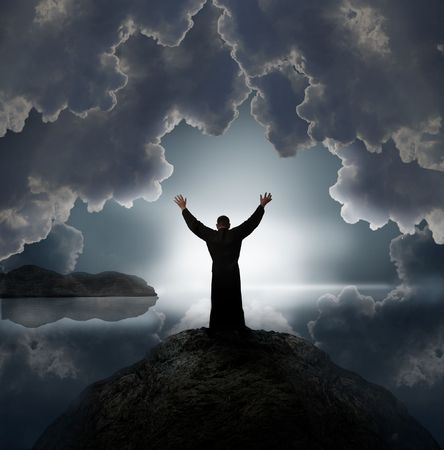Man holding arms up in praise against sunset Stock Photo