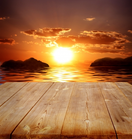 setting sun: background with  wooden bridge and sea
