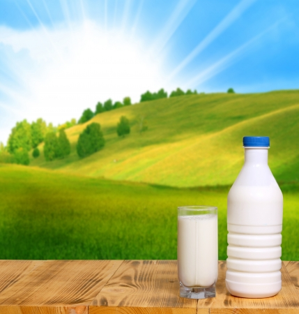Bottle of fresh milk and glass on a wooden table  photo