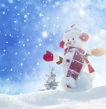 Happy snowman standing in winter christmas landscape