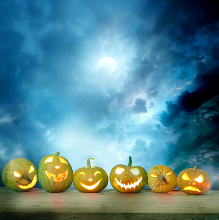 haunted: Spooky halloween pumpkins on a wooden table