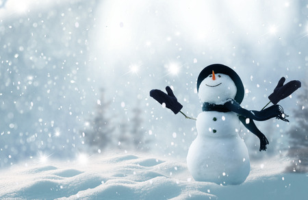 Merry christmas and happy new year greeting card with copy-space.Happy snowman standing in winter christmas landscape.Snow background Фото со стока