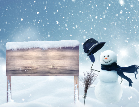 Merry Christmas and happy New Year greeting card with wooden signboard in snow. Snowman standing in winter Christmas landscape.Winter background