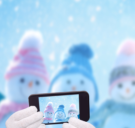 Merry christmas and happy new year greeting card Three happy snowmen making selfie on smartphone.