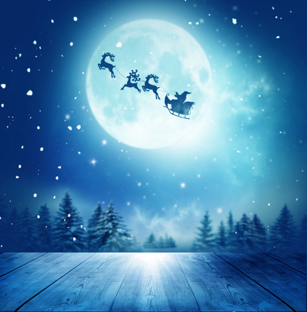 Merry christmas and happy new year greeting card with table. Santa and his sleigh flying over snowy landscape  스톡 콘텐츠