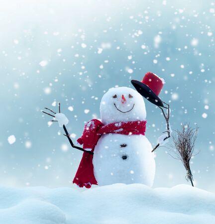 Glücklicher Schneemann, der in der Winterlandschaft steht. Schneehintergrund Standard-Bild