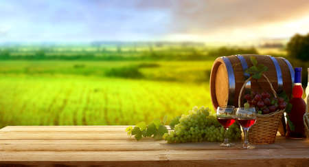 Wine and vineyard in sunset.Colorful grapes in basket. Barrel, red and white wine bottle and glass on wooden table. Rustic landscape panorama at sunset Banco de Imagens