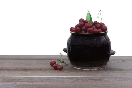 Fresh cherry in a pot on wooden table isolated on white background