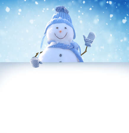 Merry Christmas and happy New Year greeting card. Snowman standing in winter Christmas landscape and points to a white billboard.