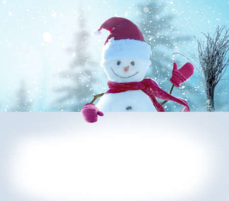 Merry Christmas and happy New Year greeting card. Snowman standing in winter Christmas landscape and point to a white billboard.