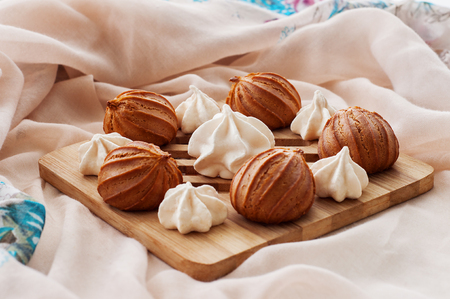 kiss biscuits: Meringues and eclairs on a wooden board