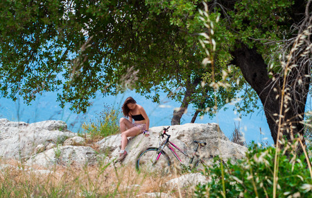 bycicle: Young woman sitting on the stone nearby the bycicle