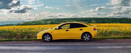 Orenbourg, Russie-Juillet 2015: Mazda voiture jaune sur la route le long du champ de tournesols Éditoriale