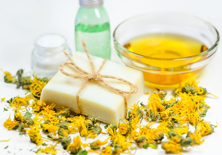 olive skin: Natural soap bar on dry yellow flowers at olive oil and bottles background. Spa treatment and skin care