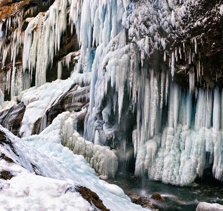 kavkaz: Frozen ice waterfall on rocky wall in winter