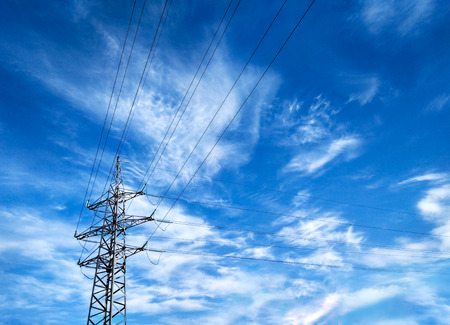 Perspective view of overhead power line with electrical wires forming frame with copy-space at blue sky background