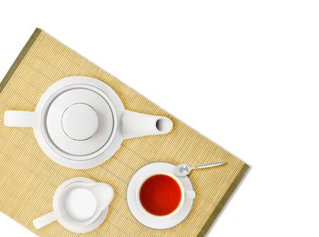 Top view of tea pot, cup and milk jug on table bamboo mat background. Hot drink ingredients isolated on white