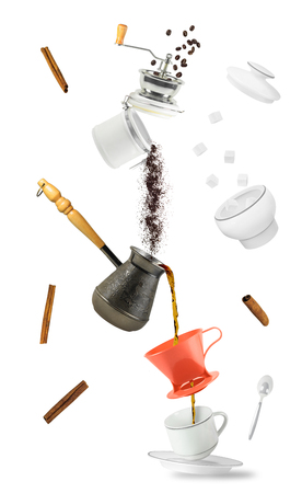 Coffee flowing into cup from turkish brewing pot and ground coffee falling from coffee mill. Flying hot drink and kitchen utensil isolated on white background Stock fotó