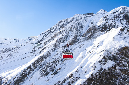 Old pendulum cable way at mountains landscape and blue sky background at winter day in ski resort