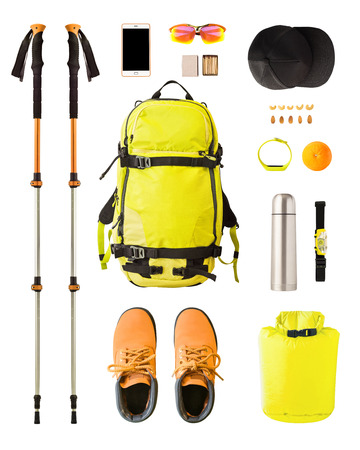 Flat lay of sport equipment and gear for hiking and trekking. Top view of walking poles, backpack, food, boots, etc. isolated on white background Stock Photo