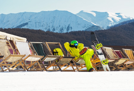 Young man with snowboard sitting and relaxing on deckchair at mountains background in ski resort Stock Photo