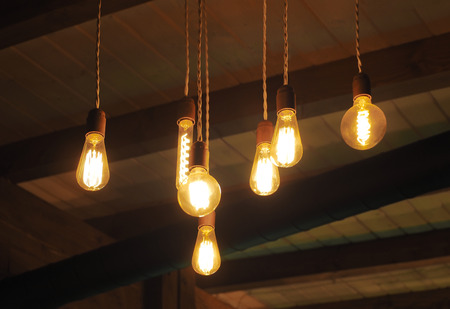 Vintage Edison filament bulbs hanging from ceiling. Antique light lamps for atmospheric interior decoration