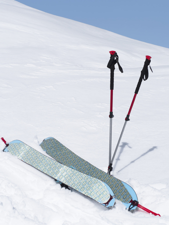 Splitboard halves with climbing skins and trekking poles at white snow background
