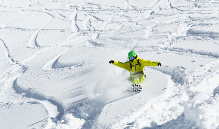Young man flying on snowboard on powder day at white snowy background