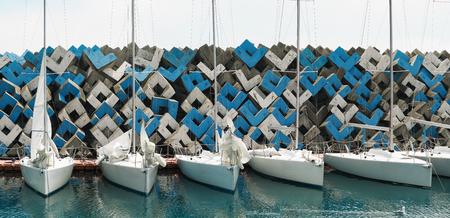 Anchored sailing boats for regatta at breakwater background in sea port Archivio Fotografico