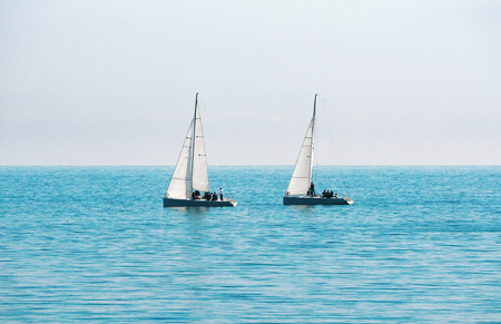 Sailing boats for regatta at blue sea and sky background
