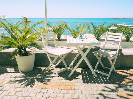 Wooden table and chairs in outdoor cafe at blue sea and palm background Banco de Imagens
