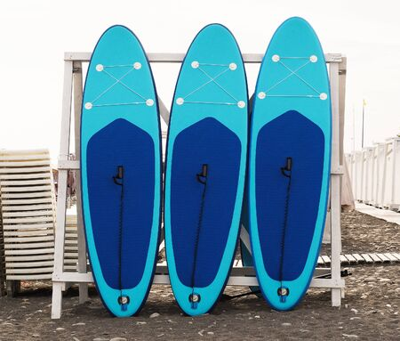 Set of stand-up paddleboard for SUP surfing in surf station on beach 免版税图像