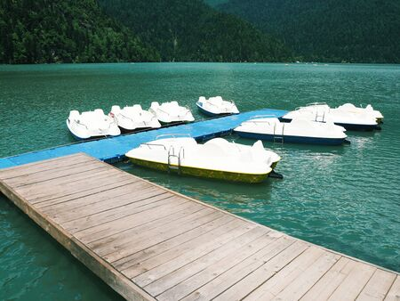 Group of anchored white catamarans at blue lake background. Water pedal boats Standard-Bild