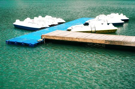 Anchored white catamarans on blue water. Pedal boats Imagens