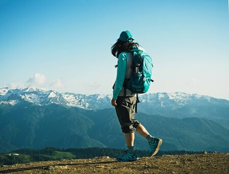 Back view of young active woman walking at mountains background. Hiking tourist with backpack in Krasnaya polyana, Sochi, Russia